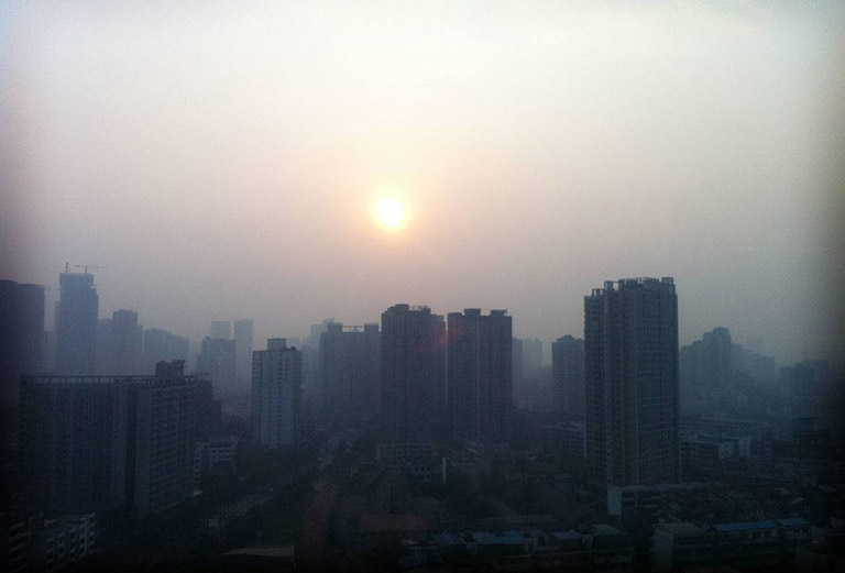 The setting sun is an ominous golden orb, smoldering above the downtown skysrapers in Shanghai. Photo Credit: UBC School of Journalism